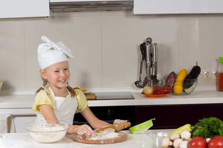 beautiful preteen girl: Happy little girl in a white chefs hat making pizza in the kitchen rolling out the dough for the base with a cheerful smile