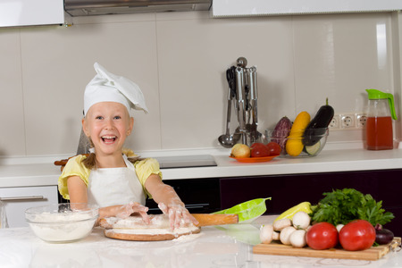 beautiful preteen girl: Cute young girl with a big smile on her face at work in the kitchen