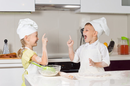 Very Happy Little Kids in Chefs Attire Playing in the Kitchen photo