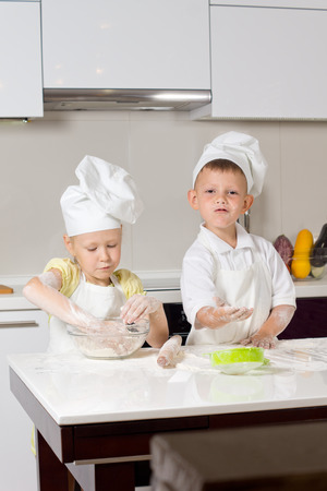 Cute White Little Chefs Baking on White Wooden Table in the Kitchen photo