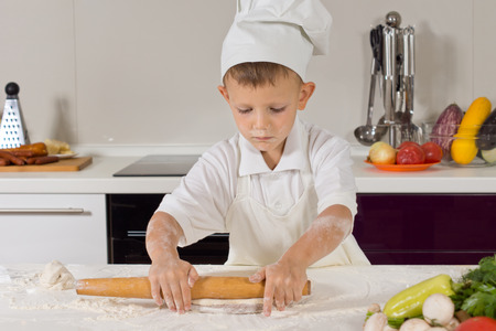 vivacious: Little boy dressed in a chefs white toque and apron standing rolling out dough in the kitchen as he makes a the base for a homemade Italian pizza Stock Photo