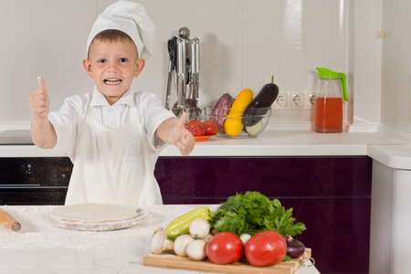 dressed for success: Excited little boy dressed in chefs clothes cooking pizza giving a thumbs up of success as he completes the base for the ingredients