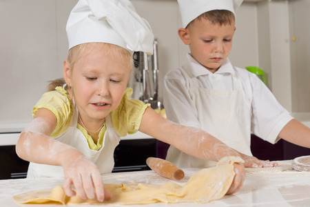 vivacious: Cute Young Chefs Busy Preparing Food to Eat at the Kitchen. Stock Photo