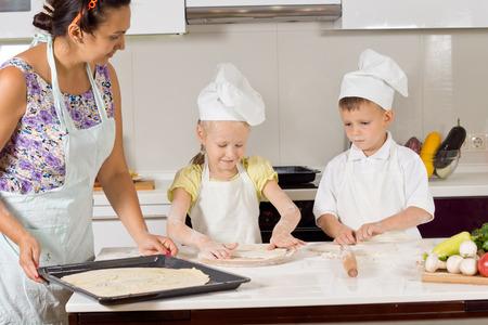2 つのかわいい子供たちはキッチンで、自家製のパイを焼くための生地を準備する母親を支援しながらシェフの制服を着ています。 写真素材