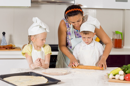 Mother Teaches How to Make Pizza to Kids Wearing Chefs Attire at the Kitchen photo