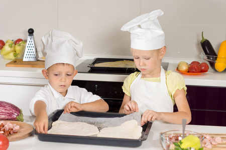 Little boy and girl in a chefs apron and toque making homemade pizza placing the rolled out pastry for the base onto a baking tray as they work as a team photo