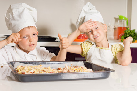 Little Chefs Tired from Baking Delicious Pizza in the Kitchen. photo