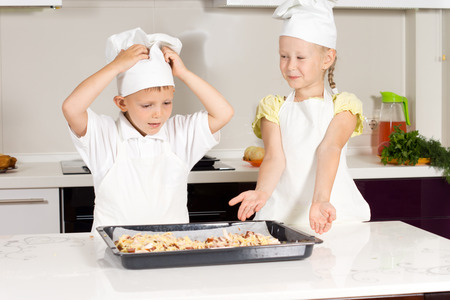 Two Cute Kids in Chefs Attire Made Appetizing Food at the Kitchen. photo