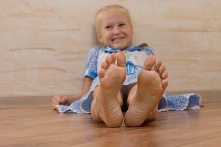 beautiful preteen girl: Smiling Young Girl Showing Feet on Camera, Isolated on Wooden Brown.
