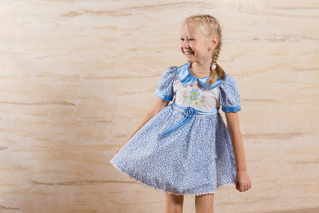 hilarity: Beautiful playful little girl with a happy smile laughing as she twirls the skirt of her blue summer frock, with copyspace