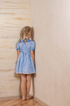 social behaviour: Little girl being punished standing in the corner facing into the wall in her pretty blue dress and bare feet Stock Photo
