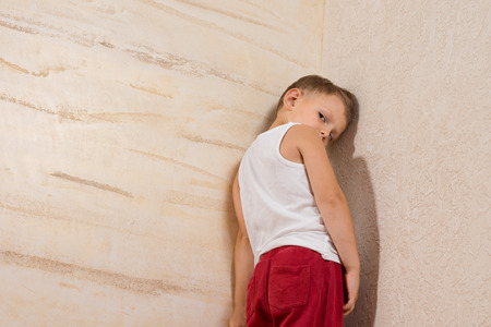 Shy Cute Little Boy Isolated on Wooden Walls. Stock Photo