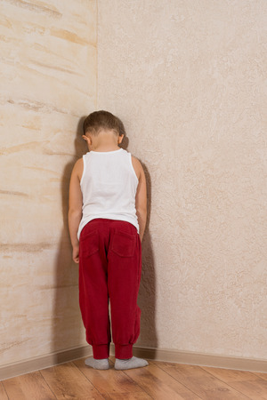White Little Boy Facing Wooden Walls. Very Shy Looking at Camera