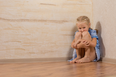 Adorable White Young Girl Sitting at House Corner, Isolated on Wooden Walls. photo