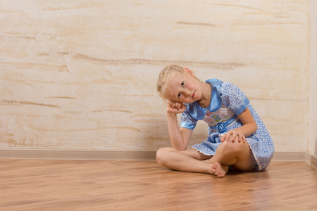 head dress: Bored little girl sitting barefoot with crossed legs on a wooden floor with her head resting on her hand watching and waiting, with copyspace