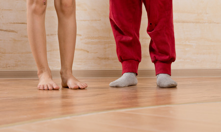 tiptoes: Two Little Kids Feet Isolated on Wooden Background. Stock Photo