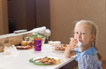 彼女はイタリアの自家製ピザの大規模なプレートを楽しむテーブルに座ると、ナプキンで口を拭く美しい小さなブロンドの女の子 写真素材