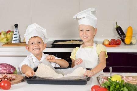 Smiling little cooks in white chefs uniforms preparing a homemade pizza for their lunch placing the rolled dough onto a baking sheet ready for the topping photo