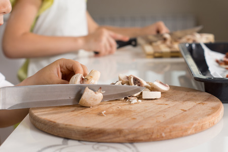 Slowly Slicing Ingredients on Round Wooden Chopping Board Stock Photo