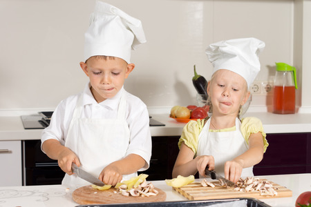 Cute Kid Chefs Busy Slicing Ingredients for Pizza at Kitchen