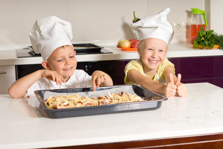 Happy Little Kids Made Pizza Successfully in the Kitchen photo