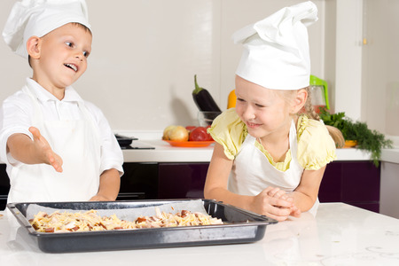 White Kids in Apron Made Delicious Pizza at the Kitchen photo