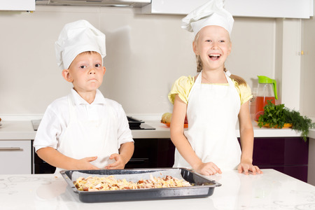 White Little Kids in Chefs Attire Made Tasty Pizza at the Kitchen photo