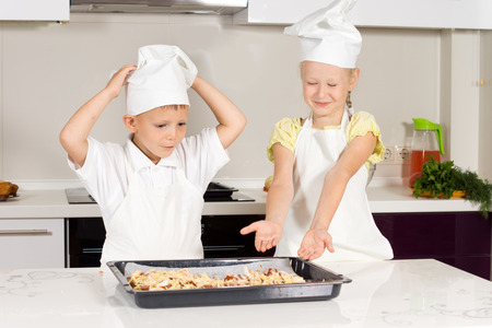 Two Little Chefs Bake Food for Lunch at the Kitchen photo