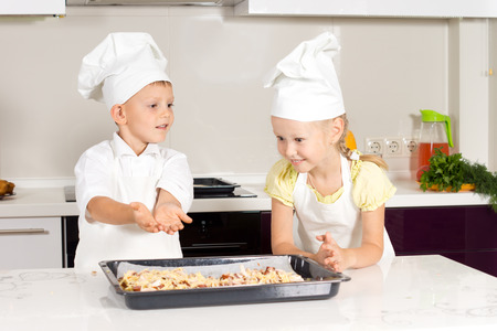 Little boy and girl in chefs uniforms adding seasoning to homemade pizza that they ave prepared themselves before putting them in the oven photo