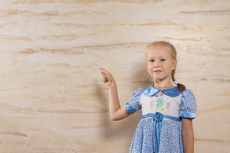 hilarity: Cute blond girl wearing a dress with floral pattern wile pointing to the wooden wall behind her Stock Photo