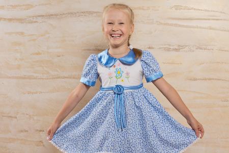 petite fille avec robe: Belle petite fille blonde f�minine tenant la jupe de sa robe bleue d'�t� �l�gant avec un sourire amical charmant