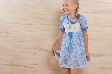 hilarity: Cute happy laughing little girl giggling as she holds onto the skirt of her pretty blue summer dress, with copyspace