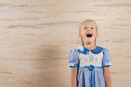 hilarity: Happy Young Girl Wearing Blue and White Dress Isolated on Wooden Wall