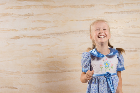 hilarity: Beautiful merry little girl in a blue summer dress with her blond hair in pigtails enjoying a good laugh, with copyspace