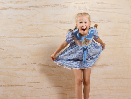 Laughing beautiful little girl taking a courtesy holding out the skirt of her stylish blue dress with a playful smile, with copyspace