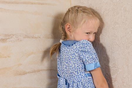 Chica de pelo Cute Little trenzado en azul y vestido blanco aislado en paredes de madera