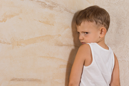 Cute Little Mad Boy Wearing White Undershirt Isolated on Light Brown Walls Stock Photo