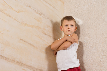Serious Little White Kid Wearing Undershirt Isolated on Wooden Walls photo