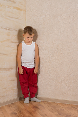 lonely boy: Cute Little Mad Kid Wearing White Undershirt and Red Jogging Pants Isolated on Light Brown Wooden Walls