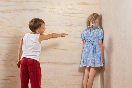 brother sister fight: Cute Little Brother Laughing To His Sister Facing on Wooden Walls