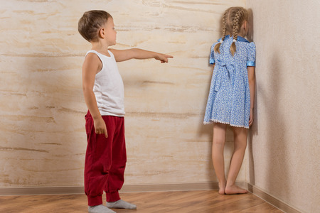 brother sister fight: Two Little Kids Playing at Home While Parents are Out, Isolated on Wooden Walls Stock Photo