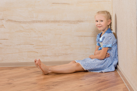 head dress: Young Beautiful Female in White and Blue Dress Sitting on Floor. Isolated on Wooden Wallls
