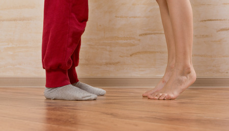 tiptoes: Two Little Feet, Face to Face, on Wooden Floor