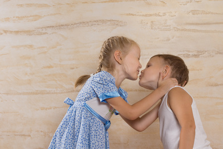sweethearts: Young sweethearts stealing a kiss celebrating their first love with a cute young blond girl stretching over to kiss a small boy
