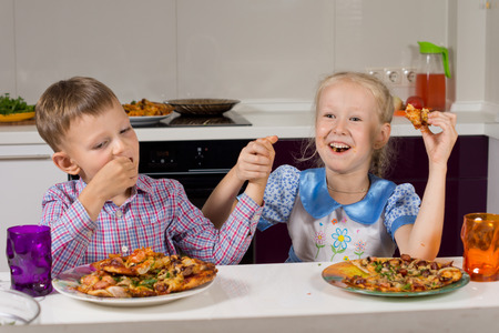 devouring: Two children celebrating eating their homemade pizza that they have cooked themselves holding hands and laughing as they sample their first slice