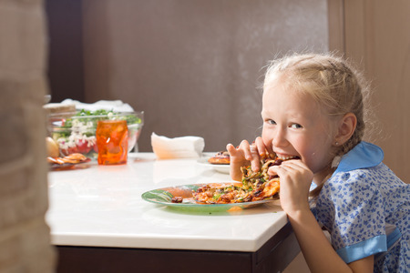 devouring: Hungry pretty little girl devouring homemade pizza looking up from taking a mouthful with a cheeky smile of enjoyment