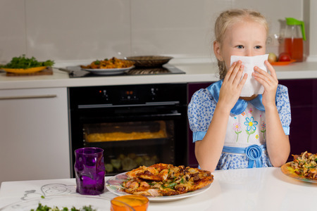Little blond girl eating a large plate of pizza sitting at the kitchen table wiping her mouth on a napkin photo