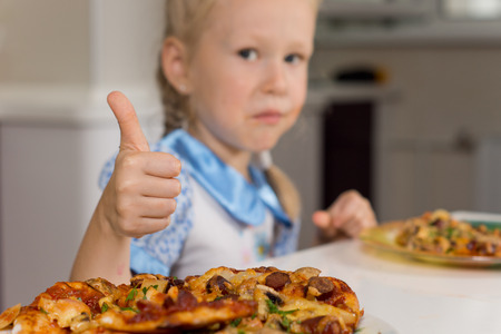 devouring: Small girl enjoying a plate of homemade pizza giving a thumbs up of approval to signal her approval and satisfaction with a tasty meal Stock Photo