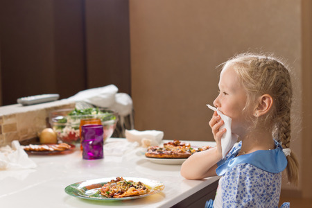 Ni�a educada con su pelo rubio en trenzas comiendo pizza hecha en casa, sentado en la mesa de limpieza cuidadosamente la boca con una servilleta Foto de archivo