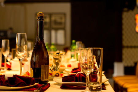 corked: Corked bottle of champagne with an empty elegant flute and glassware on a dining table in a restaurant set with formal place settings for a celebration or party